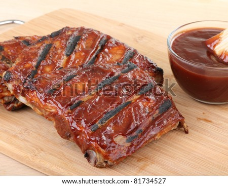 Barbecue spareribs with a bowl of sauce on a cutting board