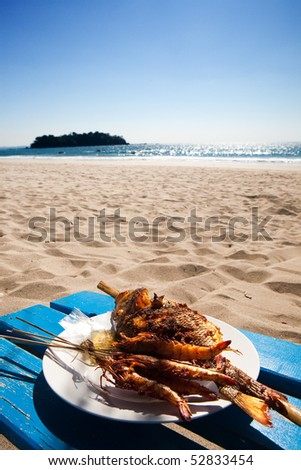 Barbecued fish and prawns by a tropical beach - stock photo