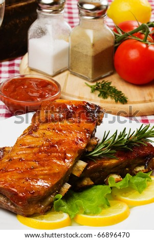 Barbecued ribs served with lettuce and lemon slices