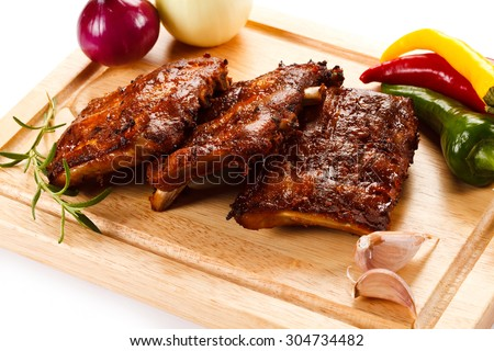 Barbecued ribs with vegetables on cutting board  - stock photo