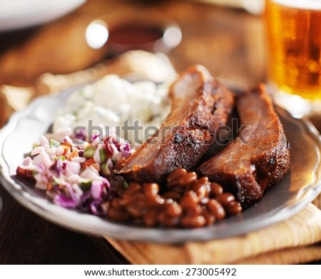 barbecued spare rib meal with beer and fixings like baked beans, cole slaw, and potato salad - stock photo