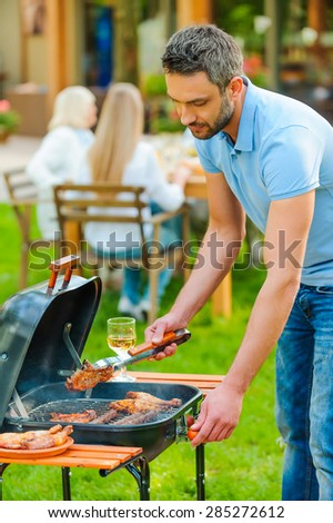 Barbecuing meat to perfection. Confident young man barbecuing meat on the grill while other members of family sitting at the dining table in the background  - stock photo
