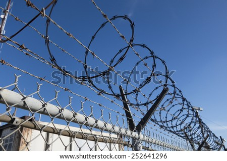 Barbed and razor wire on a fence with a security camera in the background  - stock photo