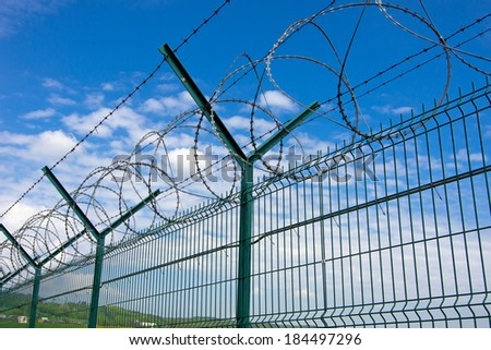 Barbed fence  against a blue sky  - stock photo