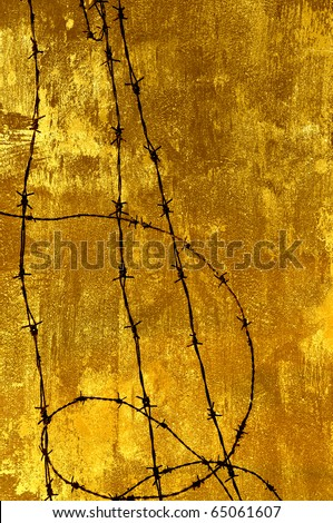 Barbed wire against a grungy old wall in sepia. - stock photo