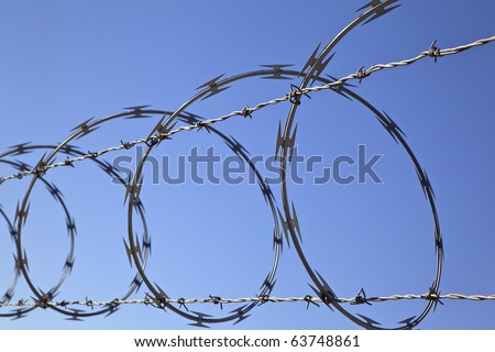 Barbed wire and concertina wire atop a fence protect a secure area. Horizontal shot. - stock photo