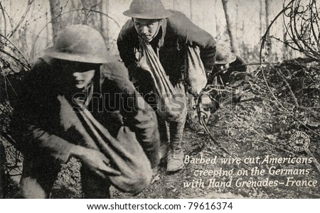 Barbed Wire Cut - Early 1900's WWI postcard depicting Americans going through cut barbed wire with bags of grenades toward Germans. - stock photo