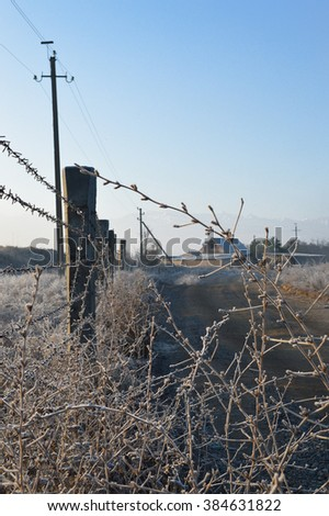 Barbed wire fence along the road of village - stock photo