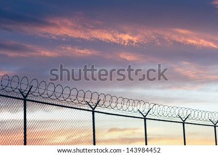 barbed wire fence and sky - stock photo