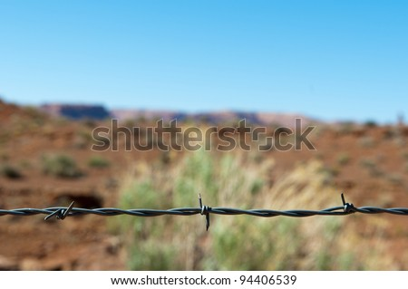 barbed wire fence made of steel in front of desert and blue sky in the USA - stock photo
