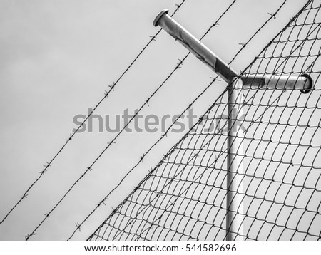 Barbed wire fence under the sky background