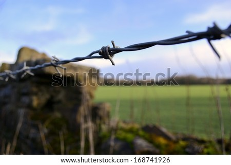 Barbed wire fence with old stone wall in background. - stock photo