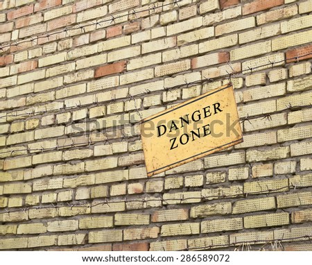 barbed wire near the danger zone with a sign - stock photo