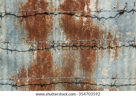 barbed wire on rusty zinc used as wall - stock photo