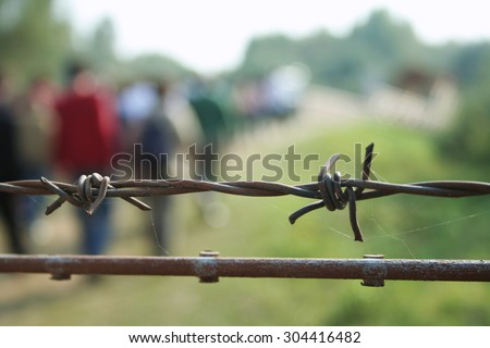 barbed wire with blurred shapes of migrants - stock photo