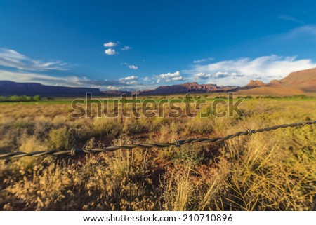 Barbed Wire with Sunset over Fisher Mesa along the road US 128 near Moab Utah   - stock photo