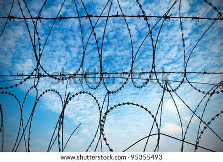 barbed wires against blue sky. - stock photo