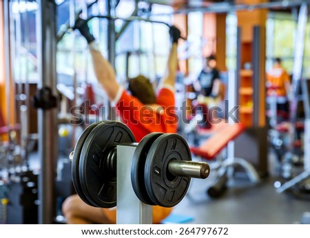 Barbell plates holder rack in the gym. On the rear background man, working out with barbell - stock photo