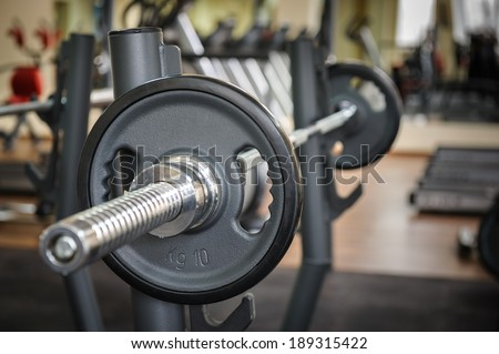 Barbell ready to workout, indooors, shallow DOF - stock photo