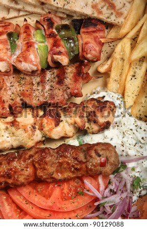 barbeque mix griil served with fries tzatziki and pita on a greek style