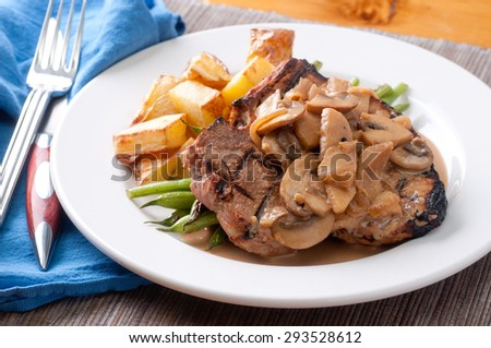 barbequed pork chops with apple mushroom sauce - stock photo