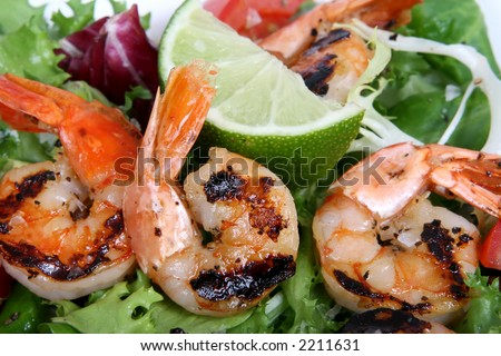Barbequed prawn salad with shrimp lettuce and green lime, macro closeup with copy space - stock photo