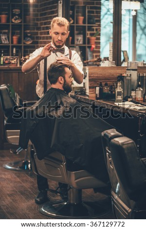 Barber at work. Full length of young bearded man getting haircut by hairdresser while sitting in chair at barbershop - stock photo