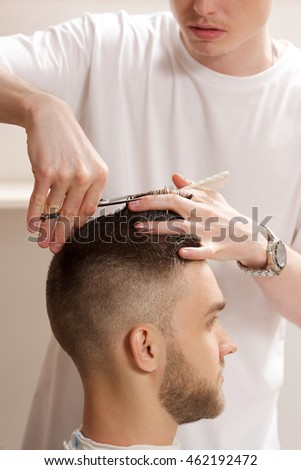 barber cuts hair with scissors on crown of handsome satisfied client in barbershop