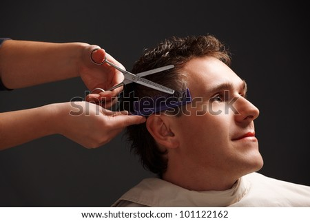 Barber cutting hair with scissors and comb, a client is a young caucasian man - stock photo