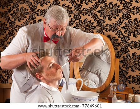 Barber cutting the mustache of a customer in an antique victorian barbershop (the antique magazine is from 1910). - stock photo