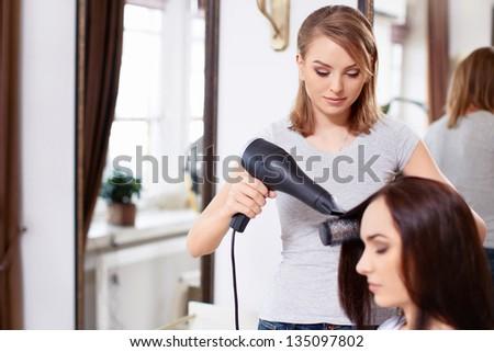 Barber hairdryer dries head girl - stock photo