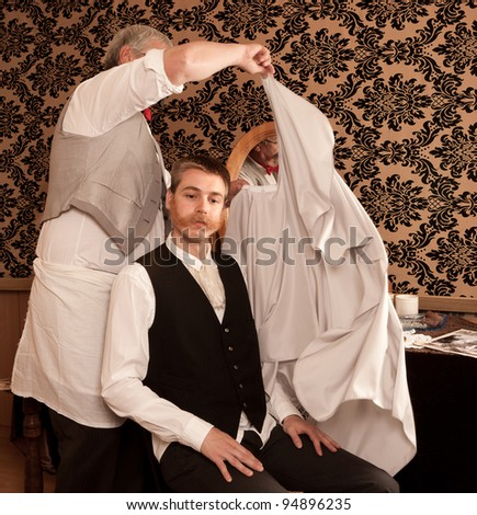 Barber putting a cape on his customer for a haircut in a victorian barbershop - stock photo