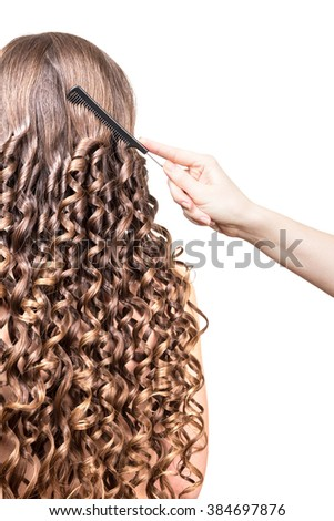 Barber's hand combing long wavy hair isolated on white background. - stock photo