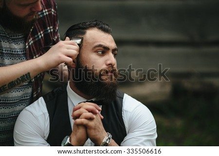 barber shaves a bearded man Outdoors