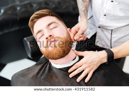Barber shaving man with straight razor in barbershop