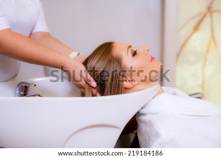 barber washes the head of a beautiful girl in a beauty salon, close-up - stock photo