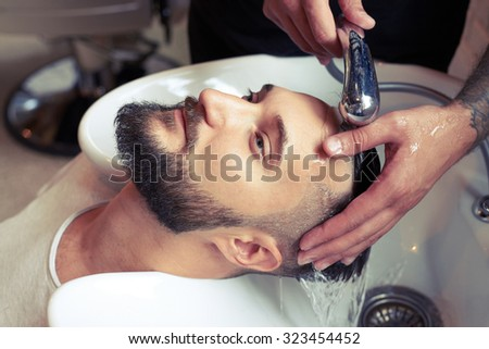 barber washing man head in barbershop - stock photo