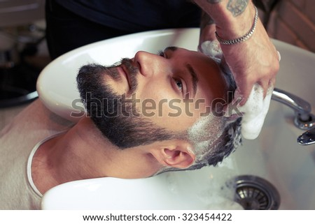 barber washing man head in stylish barbershop - stock photo