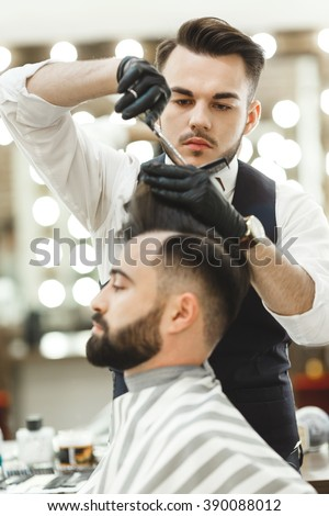 Barber with dark hair wearing white shirt, watch and black gloves doing a haircut for client with scissors at barber shop, lights at background, copy space.