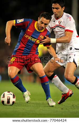 BARCELONA - APRIL 23: Xavi Hernandez of Barcelona fight with Nekounam of Osasuna during the match between FC Barcelona and Osasuna at the Nou Camp Stadium on April 23, 2011 in Barcelona, Spain - stock photo
