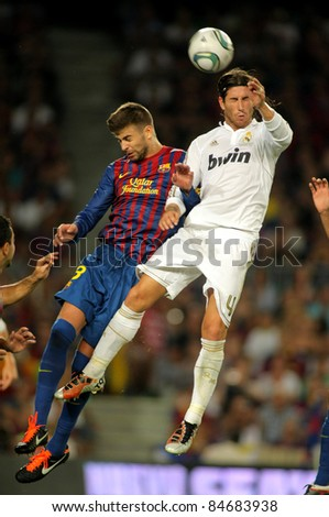 BARCELONA - AUG, 17: Gerard Pique(L) of FC Barcelona vies with Sergio Ramos(R) of Real Madrid during the Spanish Supercup football match at the New Camp Stadium in Barcelona, on August 17, 2011 - stock photo