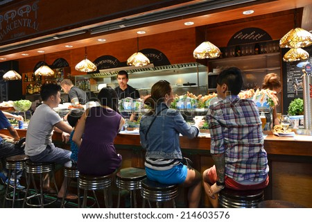 Barcelona - August 21: customers seated at a tapas bar at La Boqueria market in Barcelona, Spain on Augut 21, 2014. The market is one of the oldest in Europe and a popular tourist attraction.