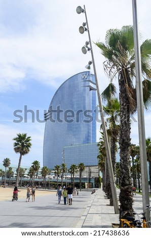 BARCELONA - AUGUST 9: Tourists enjoy the sunny weather and walking on the promenade along the Barceloneta beach on 9 August 2014 in Barcelona, Spain. This is one of the best beaches in the world.
