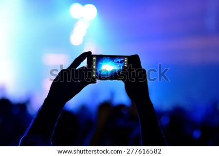 BARCELONA - JAN 29: A man takes a picture with his smartphone  in a concert at Razzmatazz venue on January 29, 2015 in Barcelona, Spain. - stock photo
