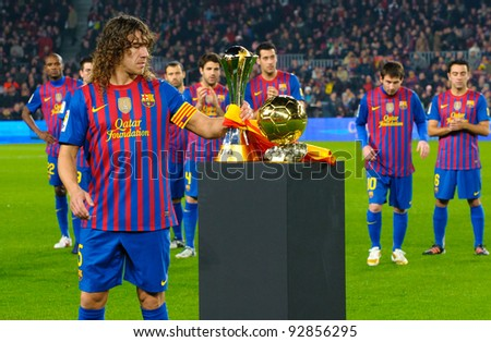 BARCELONA – JAN. 15: Carles Puyol shows the Club World Cup Footbal Trophy in Camp Nou stadium before the match between FC Barcelona vs Betis, on January 15, 2012, Barcelona, Spain. - stock photo