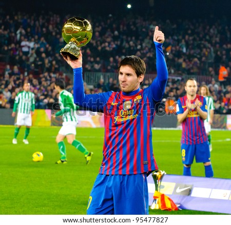 BARCELONA – JAN 15: Leo Messi poses with FIFA World Player Gold Ball Award in Camp Nou stadium before the match between FC Barcelona vs Betis, on January 15, 2012, Barcelona, Spain. - stock photo