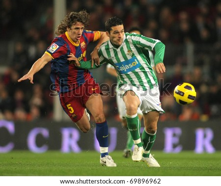 BARCELONA - JAN 12: Puyol of Barcelona fight with Molina of Betis during the match between FC Barcelona and Real Betis at the Nou Camp Stadium on January 12, 2011 in Barcelona, Spain - stock photo