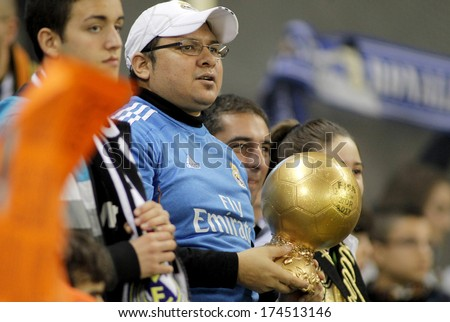 BARCELONA - JAN, 12: Supporter of Real Madrid holds up a imitation of golden ball trophy during a Spanish League match at the Estadi Cornella on January 12, 2014 in Barcelona, Spain - stock photo