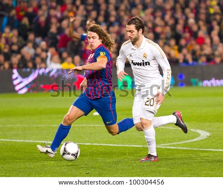 BARCELONA - JANUARY 25: Carles Puyol (L) and Gonzalo Higuain in action during the Spanish Cup match between FC Barcelona and Real Madrid, final score 2 - 2, on January 25, 2012, in Barcelona, Spain. - stock photo