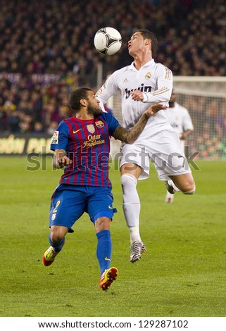BARCELONA - JANUARY 25: Dani Alves (L) and Cristiano Ronaldo in action at the Spanish Cup match between FC Barcelona and Real Madrid, final score 2 - 2, on January 25, 2012, in Barcelona, Spain. - stock photo